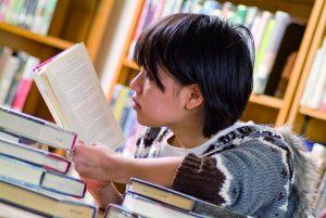 Junge liest in Büchern.
