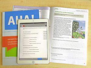 """Tisch mit aufgeschlagenem Arbeitsheft """"AHA!"""" und eBook pro auf Tablet"""