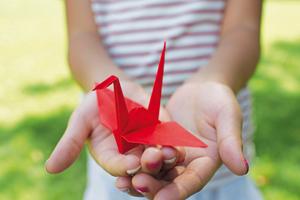 Mädchen hält Origami-Papierkranich in den Händen
