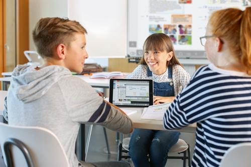 Schüler sitzen am Tisch und arbeiten mit einem Tablet