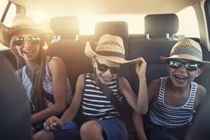 Lachende Kinder auf dem Rücksitz eines Autos, Urlaubsstimmung